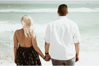 Photograph of a women and man holding hands looking out over the sea together.