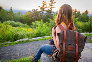 Photograph of a women sitting on a rock with a rucksack on her back looking over the woods.